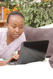 Mujer joven hermosa que usa la computadora portátil Imagen de archivo