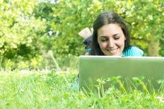 Mujer joven hermosa que usa la computadora portátil Imagenes de archivo
