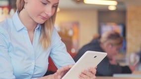 Mujer joven hermosa que usa la pantalla táctil de la tableta del ipad en café almacen de video