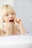 Mujer joven hermosa que usa la seda dental Fotografía de archivo libre de regalías
