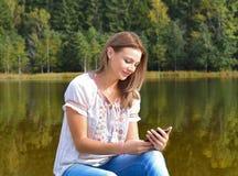 Mujer joven hermosa que usa smartphone cerca de un lago Imagen de archivo libre de regalías