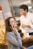 Mujer joven hermosa que usa su teléfono móvil en el co Fotografía de archivo libre de regalías