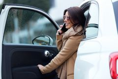 Mujer joven hermosa que usa su teléfono móvil en el coche Fotos de archivo libres de regalías