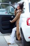 Mujer joven hermosa que usa su teléfono móvil en el coche Fotos de archivo