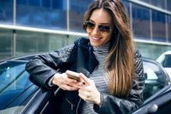 Mujer joven hermosa que usa su teléfono móvil en el coche Imagen de archivo