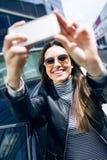 Mujer joven hermosa que usa su teléfono móvil en el coche Imagenes de archivo