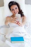 Mujer joven hermosa que usa su teléfono móvil en la cama Fotos de archivo libres de regalías