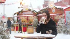 Mujer joven hermosa que usa un smartphone y bebiendo té caliente durante la feria de la Navidad almacen de metraje de vídeo