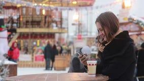 Mujer joven hermosa que usa un smartphone y bebiendo té caliente durante la feria de la Navidad delante del carrusel almacen de metraje de vídeo