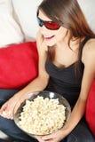 Mujer joven hermosa que ve la TV en los vidrios 3d Imagen de archivo libre de regalías