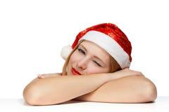 Mujer joven hermosa soñolienta en el sombrero de Papá Noel que pone en TA Foto de archivo libre de regalías