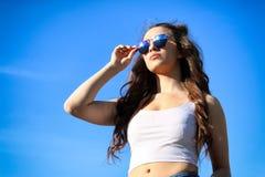 Mujer joven hermosa sobre el cielo azul Fotos de archivo