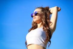 Mujer joven hermosa sobre el cielo azul Foto de archivo libre de regalías