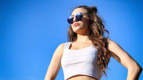 Mujer joven hermosa sobre el cielo azul Fotografía de archivo