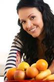 Mujer joven hermosa, sonriendo delante de la cesta de fruta Fotografía de archivo