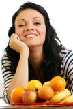 Mujer joven hermosa, sonriendo delante de la placa de la fruta Fotos de archivo