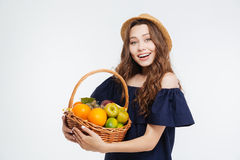 Mujer joven hermosa sonriente en el sombrero que sostiene la cesta con las frutas Foto de archivo libre de regalías