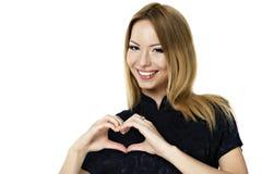 Mujer joven hermosa sonriente feliz que muestra gesto del símbolo del corazón Fotos de archivo