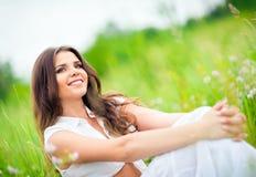 Mujer joven hermosa sonriente feliz que se sienta entre hierba y flores Fotos de archivo