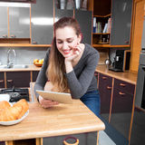 Mujer joven hermosa sonriente que goza leyendo su tableta en casa Foto de archivo