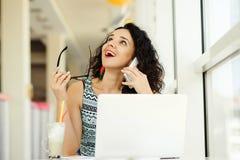 Mujer joven hermosa sonriente que usa el ordenador portátil y hablando en móvil Foto de archivo
