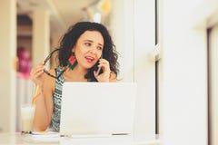 Mujer joven hermosa sonriente que usa el ordenador portátil y hablando en móvil Imagen de archivo