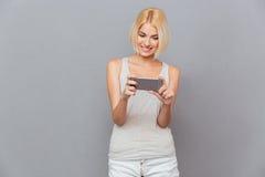 Mujer joven hermosa sonriente que usa el teléfono celular Foto de archivo libre de regalías