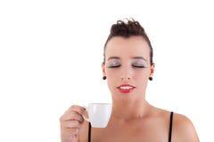 Mujer joven hermosa, tomando y disfrutando de un coffe Imagen de archivo libre de regalías