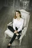 Mujer joven hermosa tranquila en un vestido blanco en casa Fotografía de archivo
