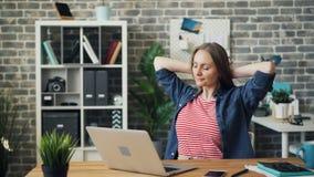Mujer joven hermosa usando el ordenador portátil en la oficina entonces que descansa la sonrisa de pensamiento almacen de video