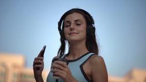 Mujer joven hermosa usando el teléfono elegante, mensajes que mecanografían, escuchando la música, café de consumición mientras q almacen de metraje de vídeo