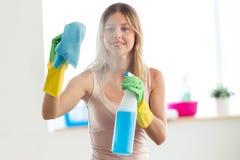 Mujer joven hermosa usando un plumero y un espray y la sonrisa mientras que limpia ventanas en casa imagen de archivo libre de regalías