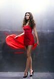 Mujer joven, hermosa y apasionada en un vestido ondulado, largo Foto de archivo