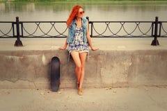 Mujer joven hermosa y de la moda que presenta con un monopatín Imagenes de archivo