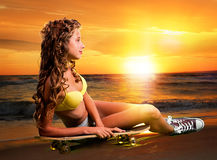 Mujer joven hermosa y de la moda que presenta en la puesta del sol con el monopatín Imagen de archivo libre de regalías