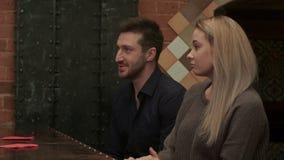 Mujer joven hermosa y hombre hermoso en la barra que habla con el camarero metrajes