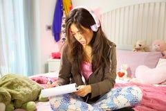 Mujer joven hispánica que estudia en cama mientras que música que escucha Imagenes de archivo