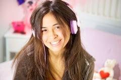 Mujer joven hispánica que estudia en cama mientras que primer sonriente de la música que escucha Fotos de archivo