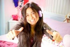 Mujer joven hispánica que estudia en cama mientras que pulgar sonriente de la música que escucha para arriba Foto de archivo libre de regalías