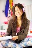 Mujer joven hispánica que estudia en cama mientras que sonrisa de la música que escucha Imagen de archivo