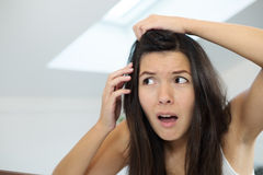Mujer joven horrorizada que mira en el espejo Imagenes de archivo
