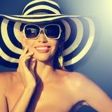 Mujer joven imponente en sombrero y gafas de sol elegantes imagenes de archivo