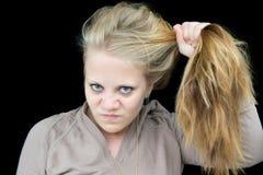 Mujer joven infeliz con su pelo Imagenes de archivo