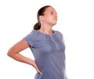 Mujer joven infeliz con un dolor de espalda terrible Imagen de archivo libre de regalías