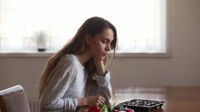 Mujer joven infeliz dudosa que elige entre la ensalada y los caramelos almacen de metraje de vídeo