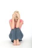 Mujer joven infeliz pensativa deprimida que se sienta solamente en el piso Imágenes de archivo libres de regalías