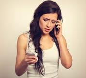 Mujer joven infeliz preocupante que habla en un teléfono móvil y typi Imagen de archivo
