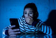Mujer joven infeliz preocupante que sufre de cyberbullying y del acoso en línea por el teléfono móvil fotografía de archivo libre de regalías