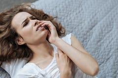Mujer joven infeliz que sufre del dolor de muelas foto de archivo