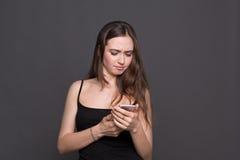 Mujer joven infeliz que usa el retrato del smartphone fotos de archivo